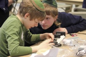 Two Kesher Tefillin participants working on their Tefillin