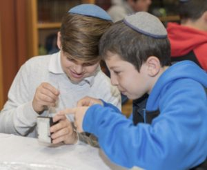 Two students working on their Tefillin during the Kesher Tefillin program