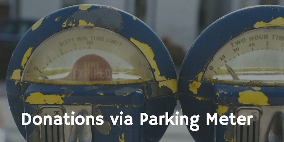Parking meters as backdrop for text Donations via Parking Meters