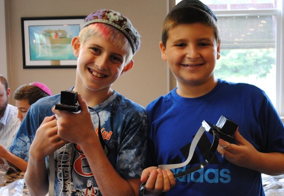 Two students holding handmade tefillin made in the Kesher Tefillin program