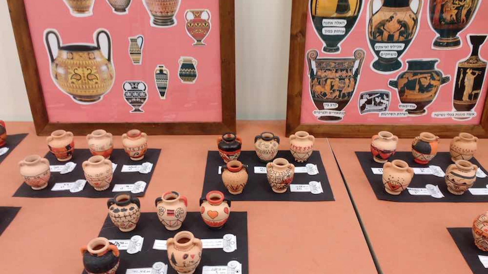 Greek mini urns made by sixth graders against a backdrop of posters showing classic Greek pottery techniques.